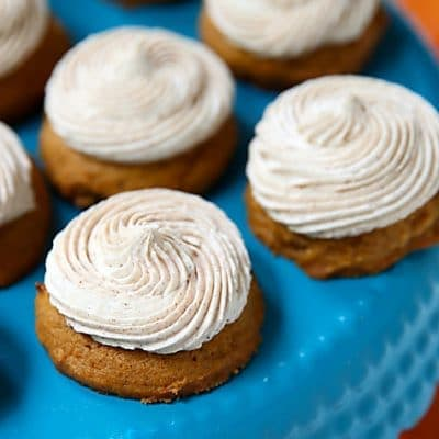 mini pumpkin cookies with cinnamon frosting on a blue cake stand