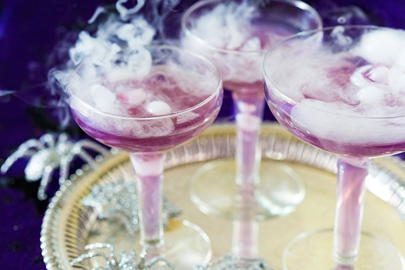 Witch's Brew Halloween Cocktail!This purple sassy Halloween cocktail is too fun and a drop of dry ice makes it even spookier! pizzazzerie.com