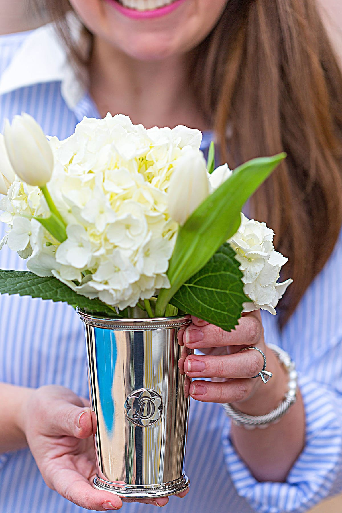 white flowers in a silver julep cup