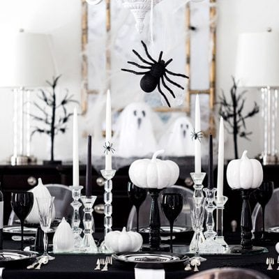 Pick a color scheme like black and white to style a chic Halloween party tablescape. Add in touches of spiders, ghosts, and cob webs for the ultimate dinner party!