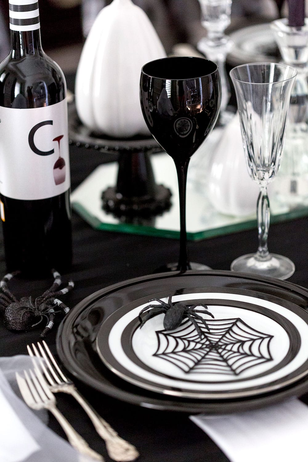 Simple die cuts from the craft store make the perfect Halloween plate toppers! I love the spider webs in this black and white Halloween party tablescape!