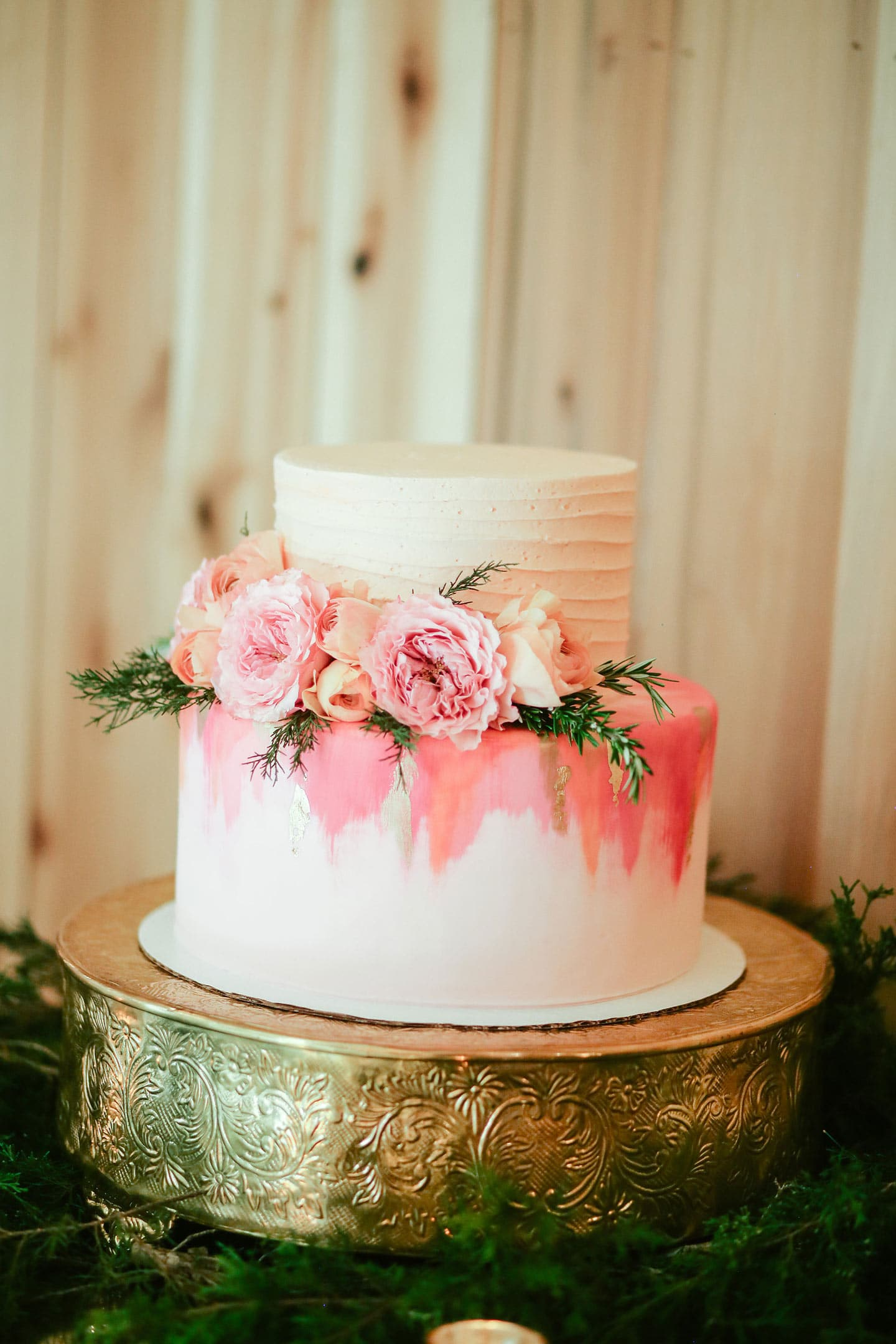 a white and pink tiered cake with flowers