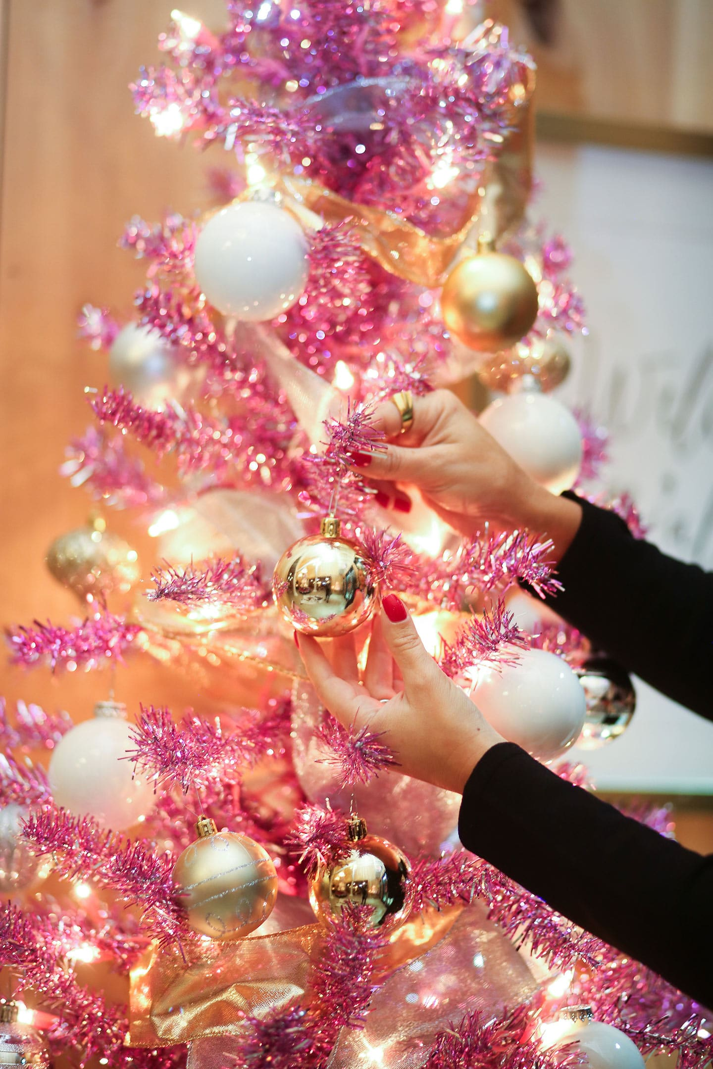 a pink tinsel christmas tree and ornaments