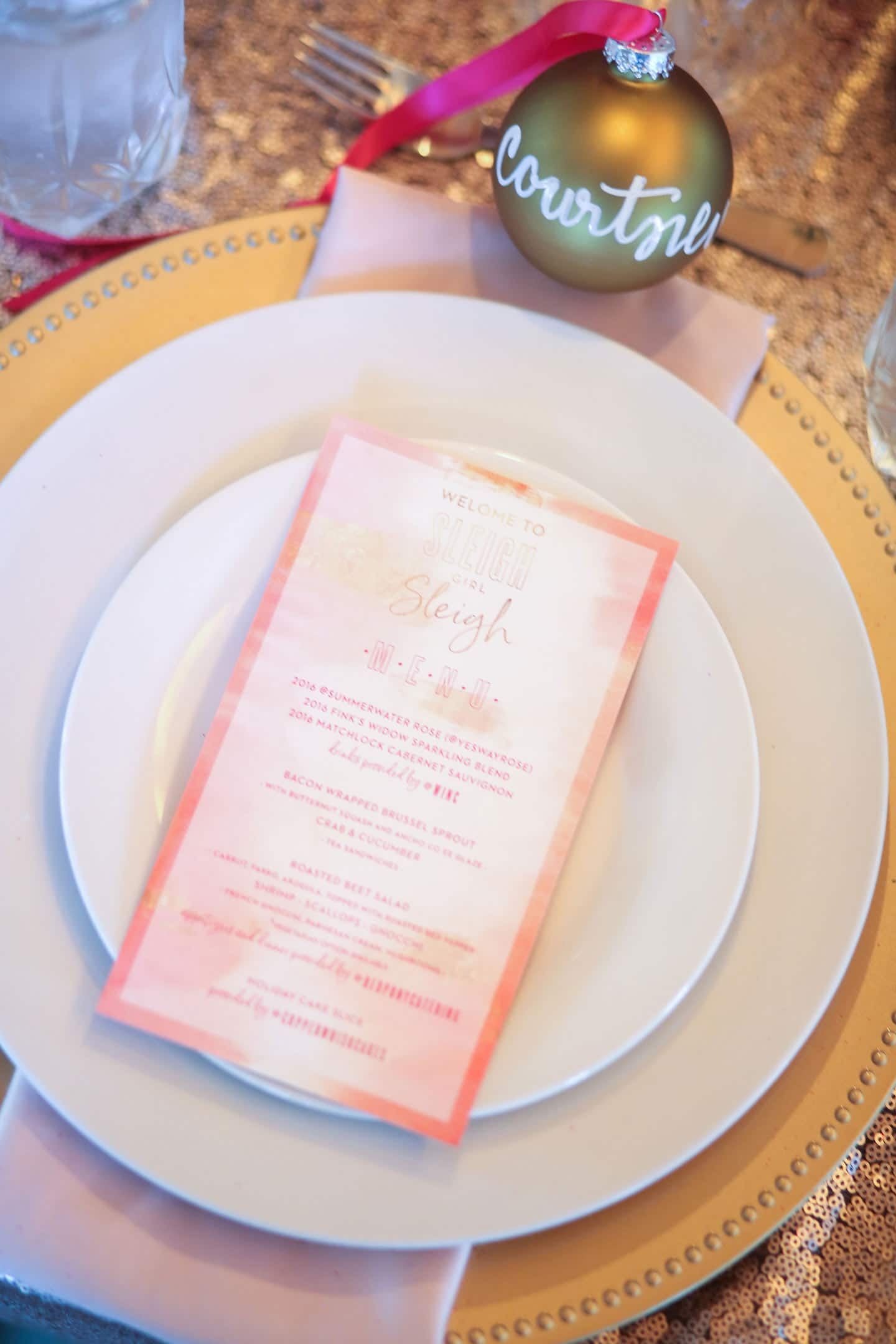 plates topped with a pink printed menu card