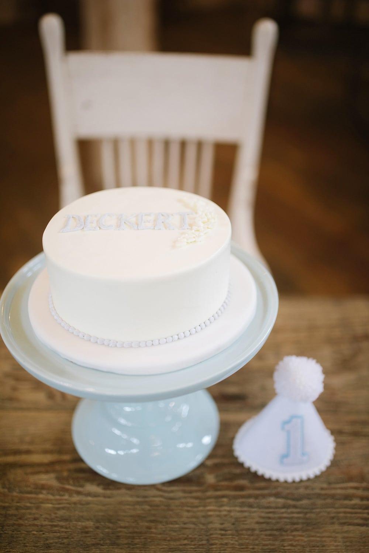 a little boy\'s smash cake on a light blue cake stand