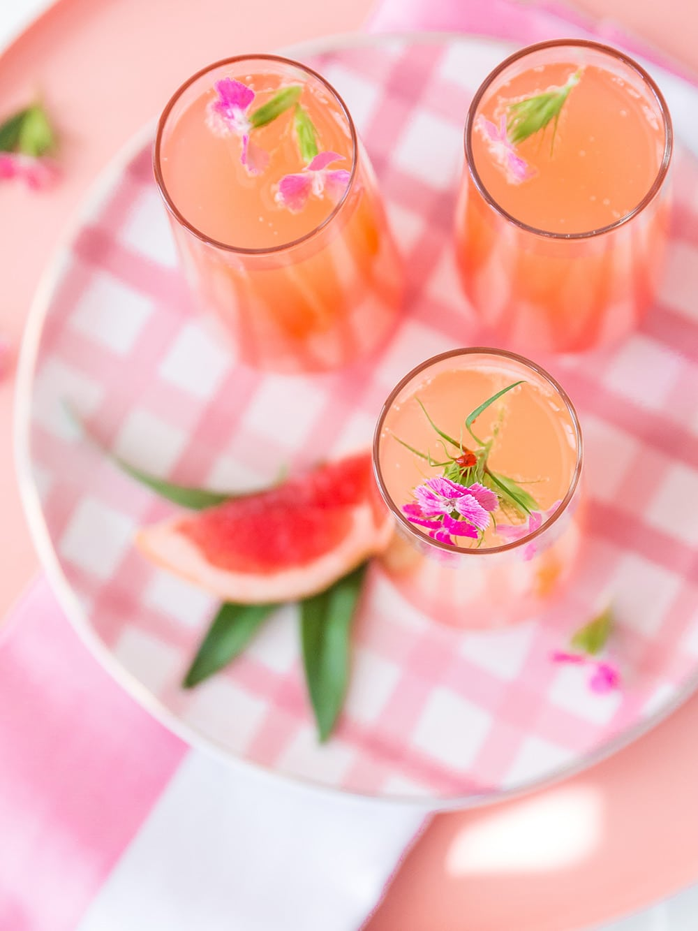 overhead view of three glasses of champagne punch on a pink check plate