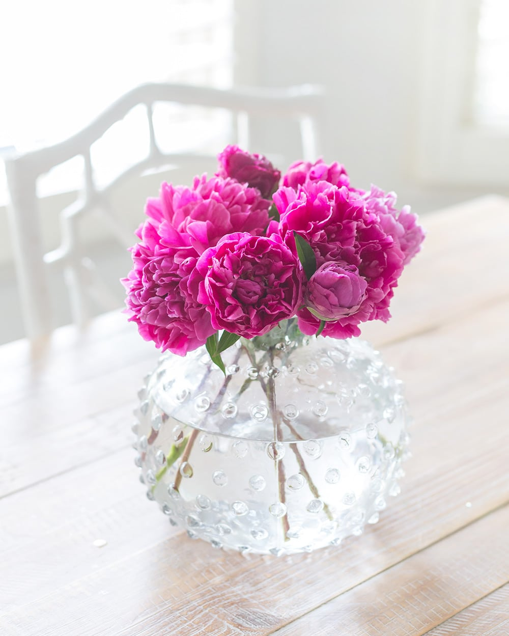 A vase filled with pink peonies sitting on a table