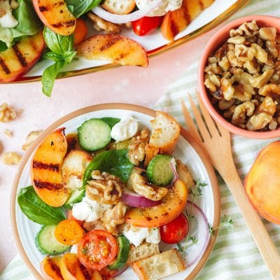a plate of grilled peach salad with walnuts