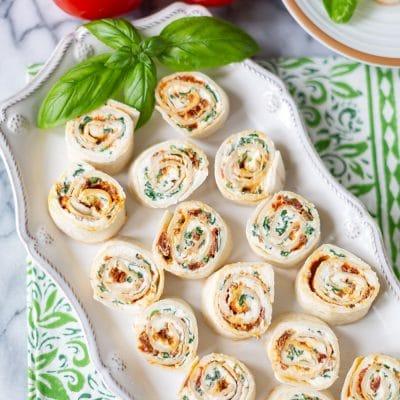 a white tray of pesto pinwheels with sun-dried tomato pesto