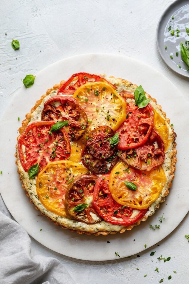 A plate of food with a slice of pizza, with Heirloom Tomato