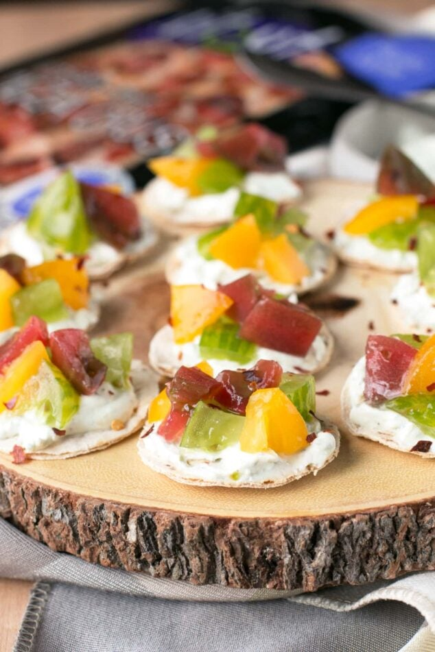 heirloom tomato and whipped goat cheese appetizers on a wood slab