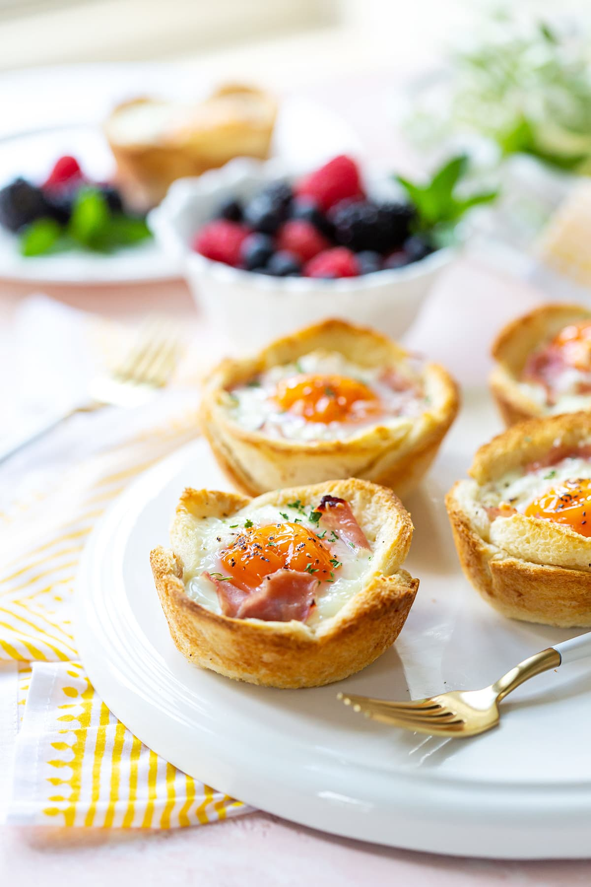 croque madame breakfast cups topped with eggs on a white round platter.