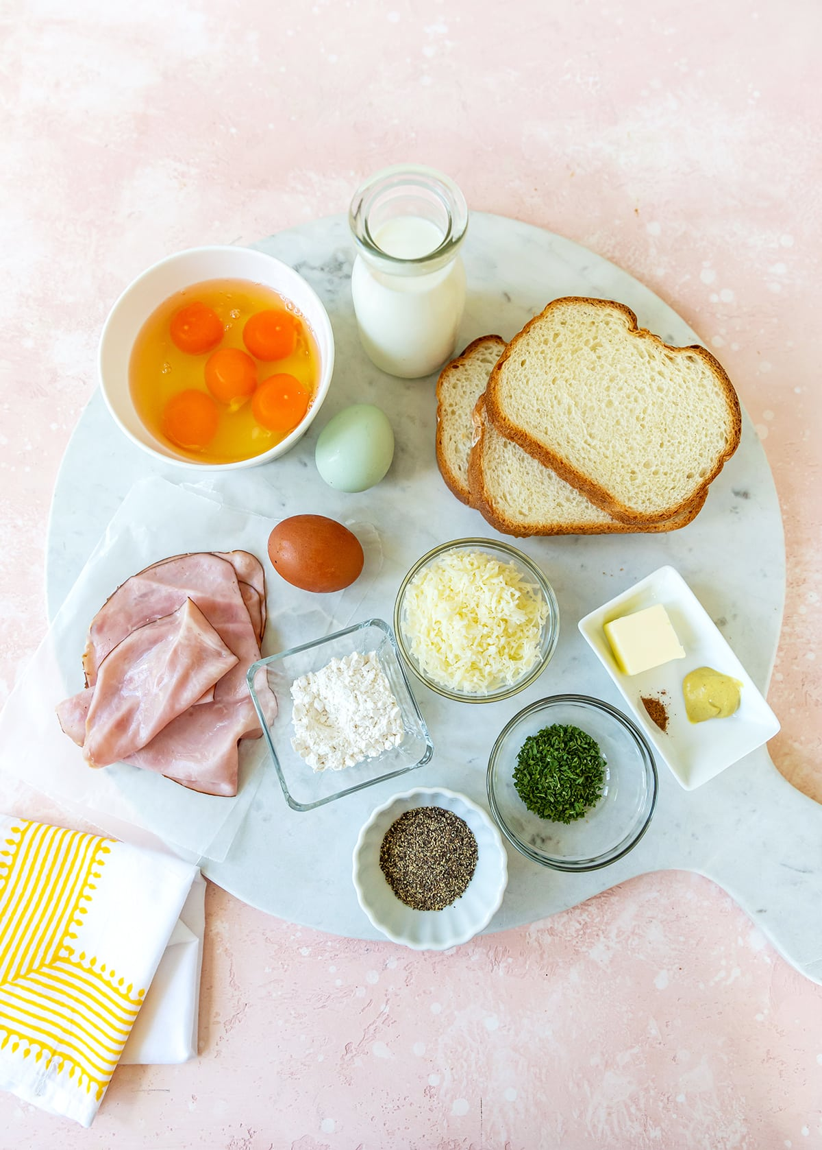 marble platter with eggs, glass of milk, bread, butter, cheese, ham and seasonings.