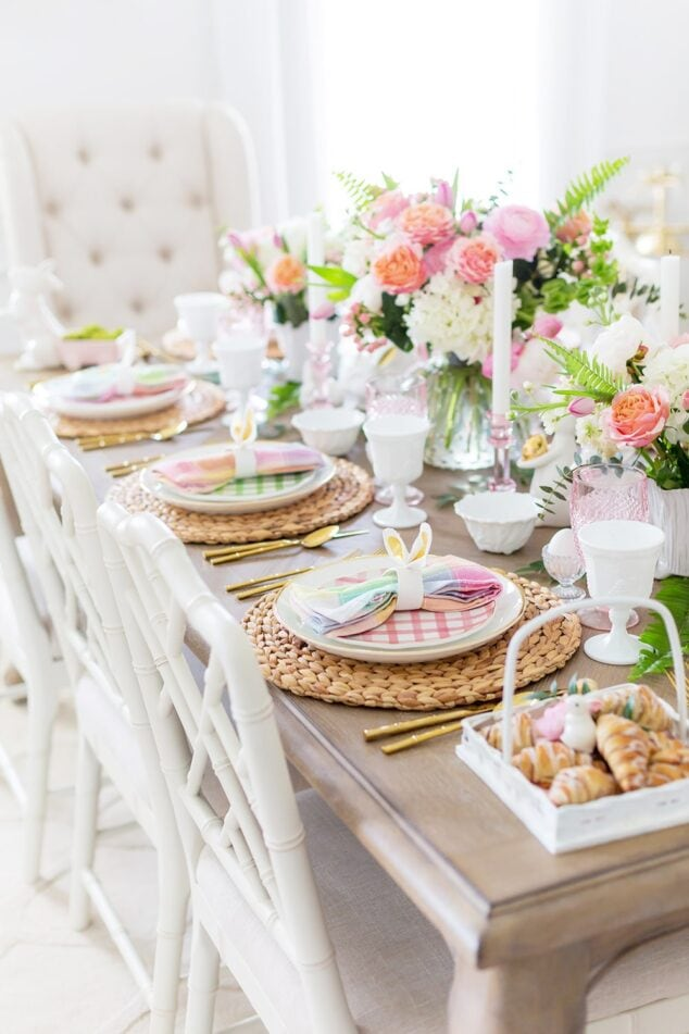 a table full of easter place settings and floral centerpiece