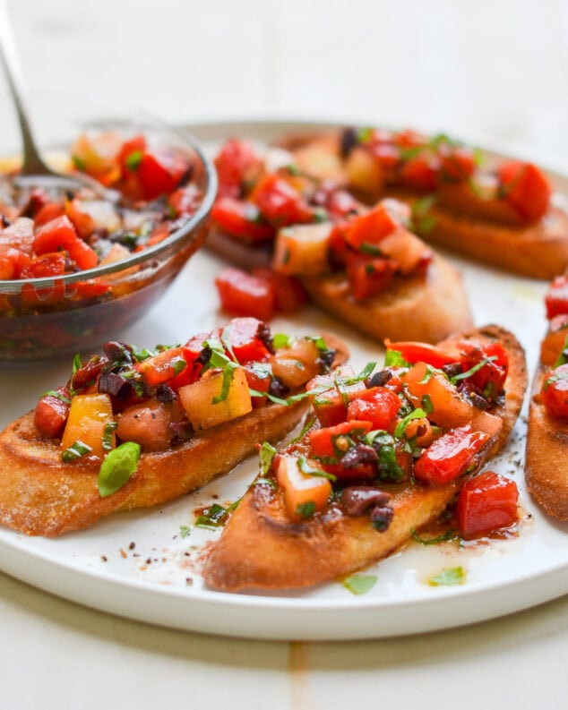 A plate of food on a table, with Tomato and Bruschetta