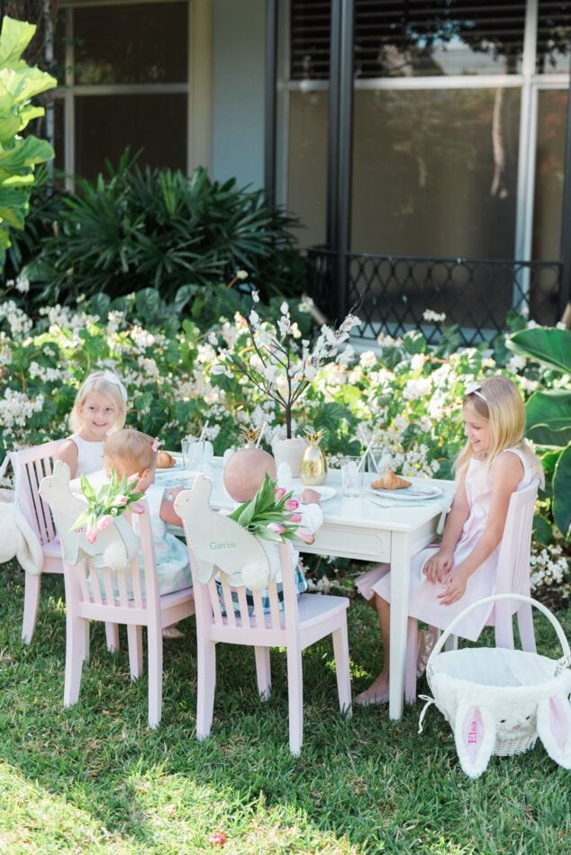 little girls sitting in a garden at a kids easter table