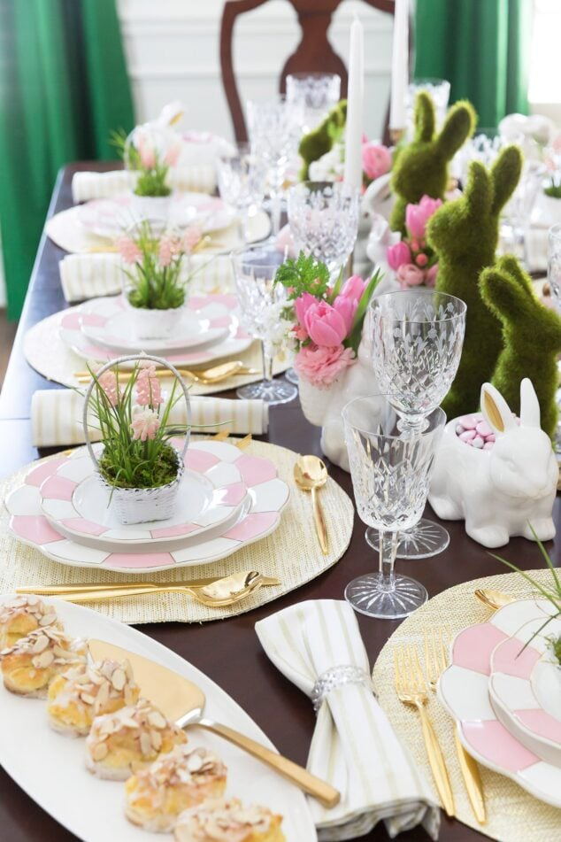 Easter table decor topped with moss bunnies and easter baskets